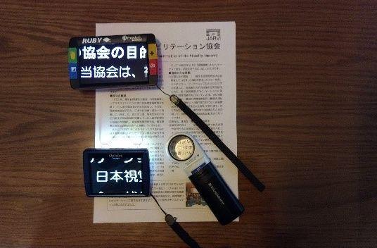 電子ルーペ(携帯型拡大読書器、左側)と光学式ルーペ(右下)