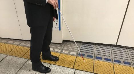 白杖を持った人が点字ブロックの上にいます