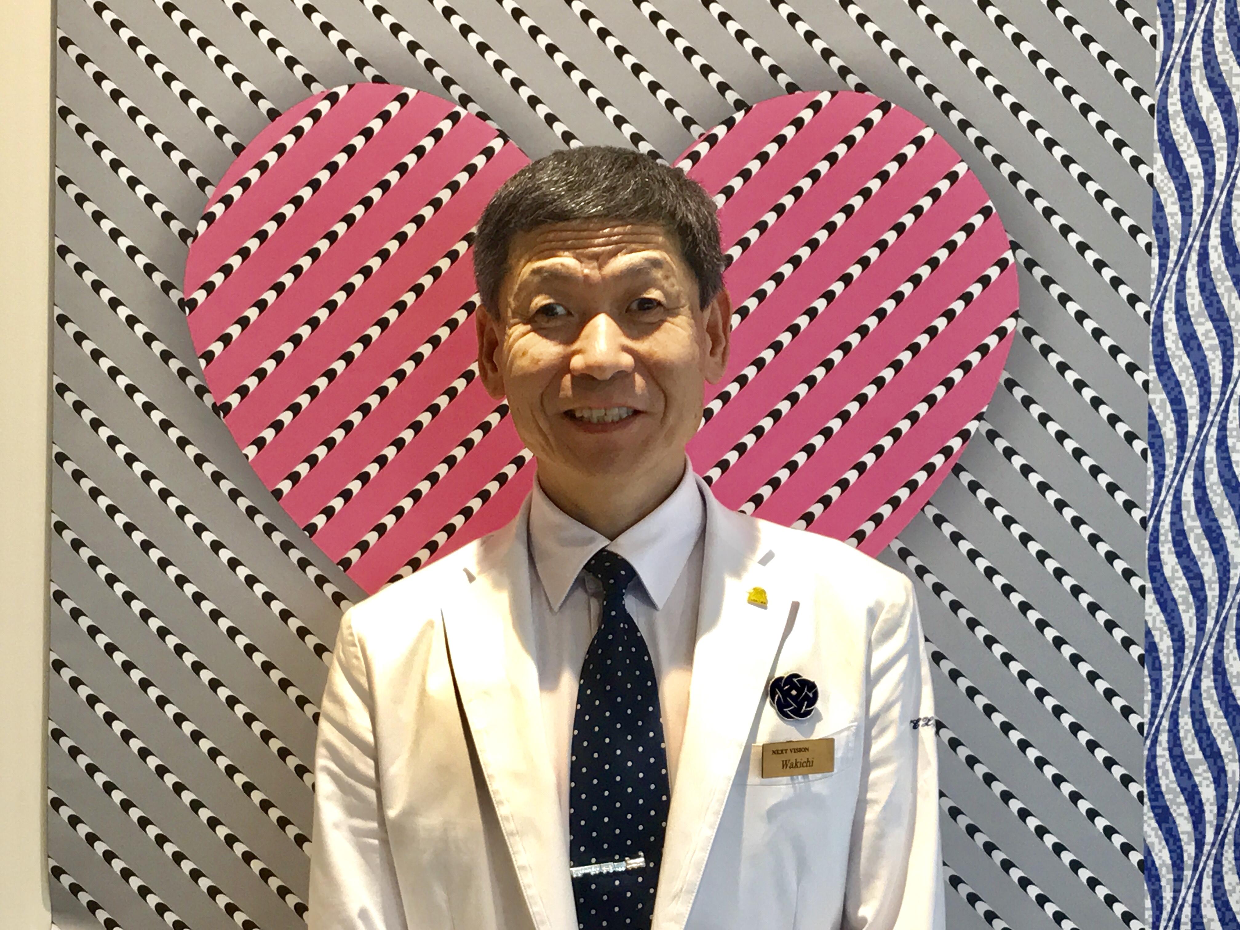 2019年度から視覚リハ協会会長に就任した和田浩一さんが、NEXTビジョンの素敵な制服を着て、ハートの描かれた壁の前に立っているところ